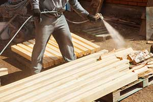 man treating fire retardant wood