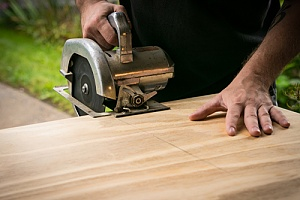 Man using saw to cut treated plywood