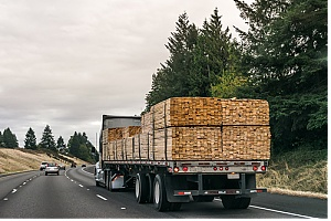 Wholesale lumber supplier truck on highway delivering lumber