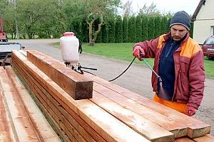 Man treating planks of wood