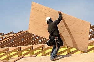 Worker building a home with plywood