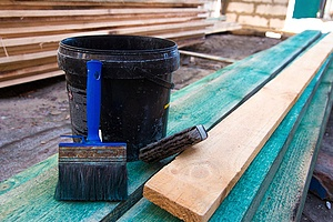 a bucket of primer that provides a layer between fire-treated wood