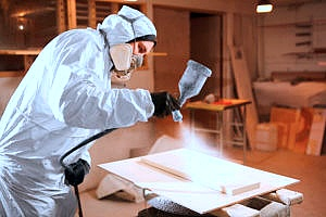 a contractor spraying a piece of fire retardant plywood