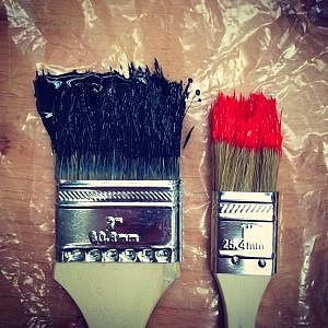 two paintbrushes to be used on southern yellow plywood