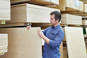man in a blue shirt choosing different types of pressure treated plywood