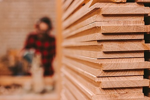 plywood stacked high with a person in a plaid shirt in the background