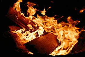 A plank of fire retardant plywood on a burning fire