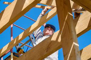 Construction worker working on a wooden frame. Buying materials like lumber from wholesale suppliers can be beneficial