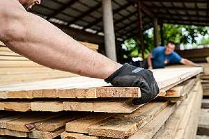 Construction workers examining lumber in a wholesale lumber warehouse