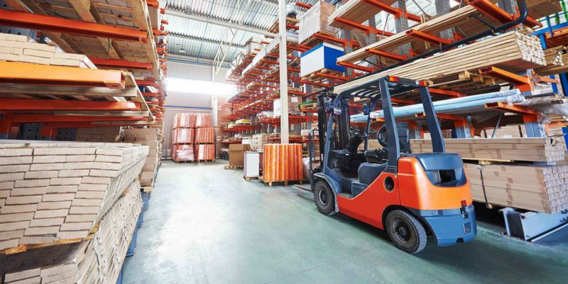 Forklift loader and stacks of lumber in a wholesale lumber supplier's warehouse