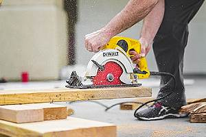 A construction worker cutting wood planks. Working with wholesale lumber suppliers is the best way