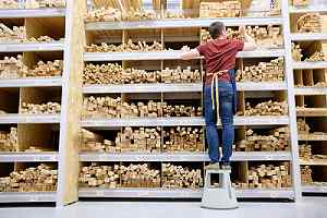 A worker arranging lumber in a storage facility of a wholesale lumber supplier