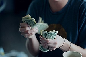 Person counting money. Wholesale suppliers tend to have better prices on higher-quality products